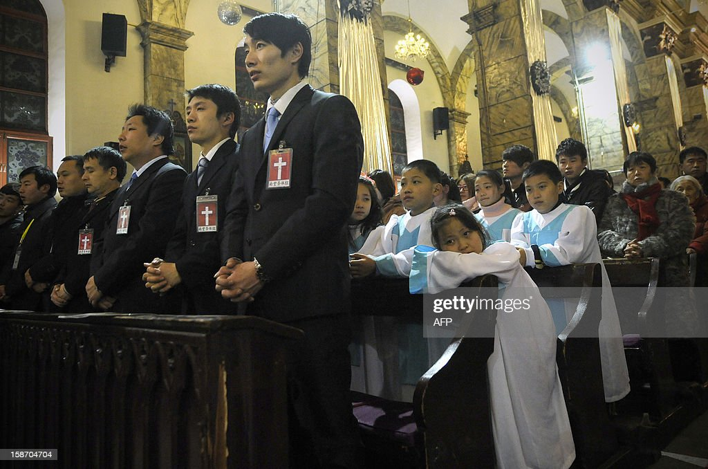 A young Chinese Christian (centre R) takes a rest during the Christmas Eve mass at a Catholic church in Beijing early on December 25, 2012. While China does not officially celebrate Christmas, its popularity continues to grow with non-Christians keen to see and feel the experience of Christmas.