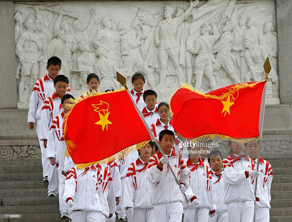 Young Chinese communist members march past the Monument to the Peoples Heroes at the Tiananmen Square in Beijing, 29 September 2007. The Chinese capital is gearing up for its 58th National Day celebration 01 October and the 17th Communist Party Congress in mid-October, which could lead to personnel changes in the top echelons of power and will set China's political and economic course for the next five years. AFP PHOTO/TEH ENG KOON
