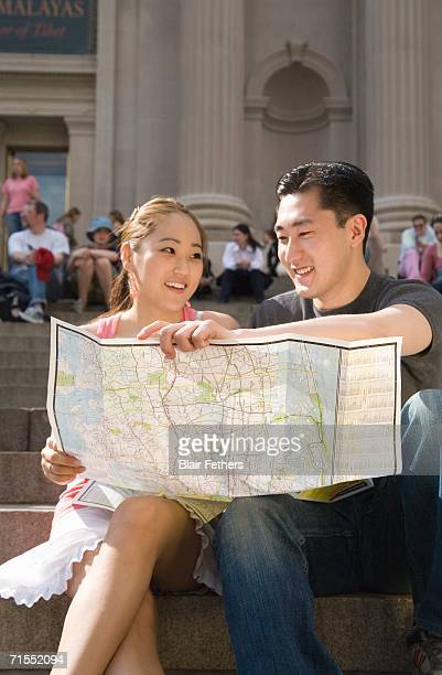 Young Chinese couple sitting on steps and holding map, New York City
