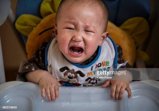 A young Chinese cries as she waits for feeding at a foster care center on April 2 2014 in Beijing China China's orphanages and foster homes used to...