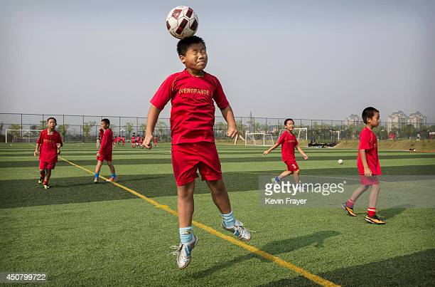 A young Chinese football player leaps up to head the ball during training at the Evergrande International Football School on June 13 2014 near...