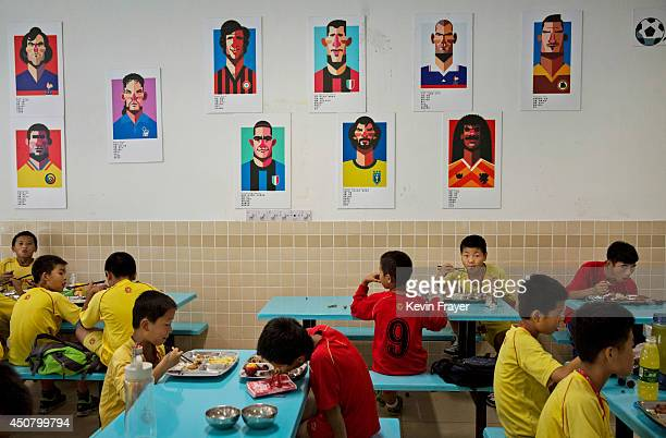 Young Chinese football players eat lunch under caricatures of famous footballers in the canteen at the Evergrande International Football School on...