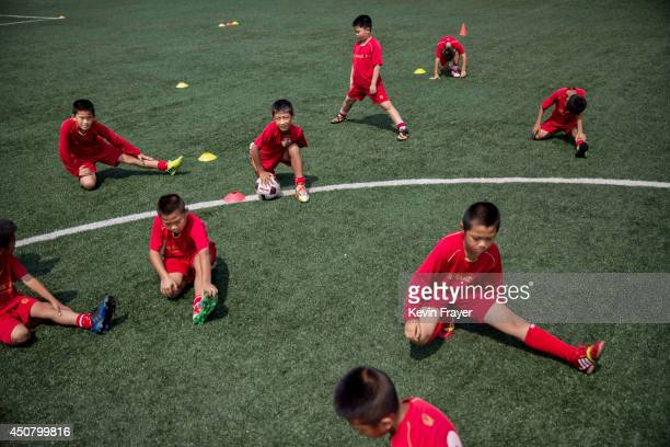 Young Chinese football players stretch during truing at the Evergrande International Football School on June 13 2014 near Qingyuan in Guangdong...
