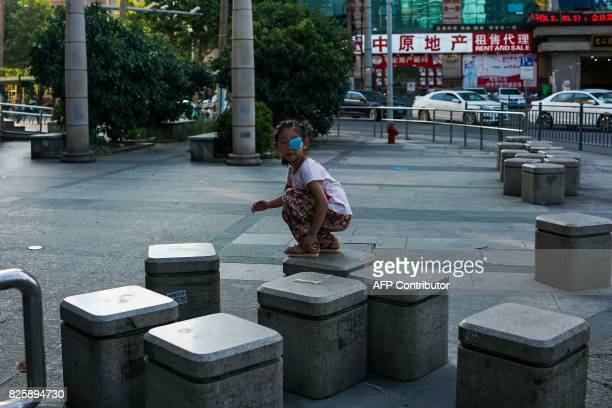 A young Chinese girl plays on the pavement in Shanghai on August 3 2017 / AFP PHOTO / CHANDAN KHANNA