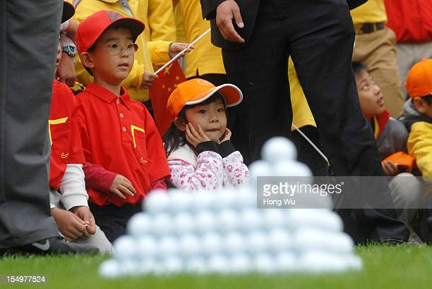 Young Chinese golf fans watch the match during the Duel of Tiger Woods and Rory McIlroy at Jinsha Lake Golf Club on October 29 2012 in Zhengzhou China