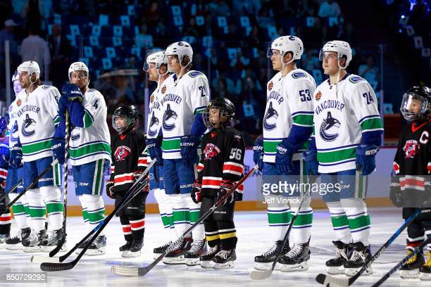 Young Chinese hockey players stand with Vancouver Canucks players before the start of the preseason game between the Vancouver Canucks and the Los...