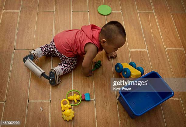 A young Chinese orphaned boy crawls wearing corrective leg braces on the floor of a foster care center on April 2 2014 in Beijing China China's...
