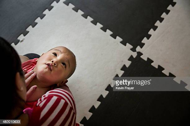 A young Chinese orphaned boy sits in the lap of a care worker at a foster care center on April 2 2014 in Beijing China China's orphanages and foster...