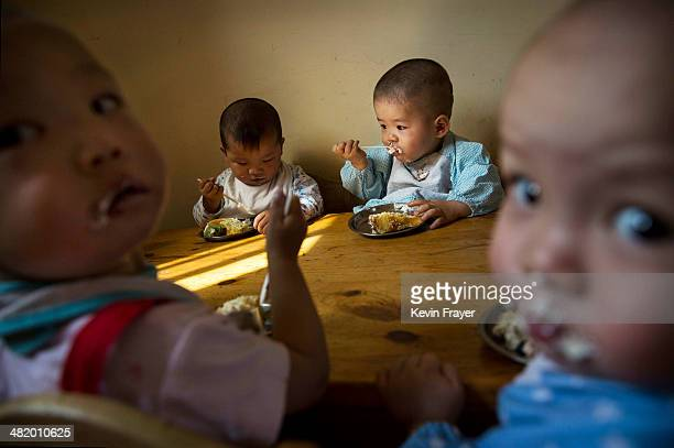Young Chinese orphaned children eat during a feeding at a foster care center on April 2 2014 in Beijing China China's orphanages and foster homes...
