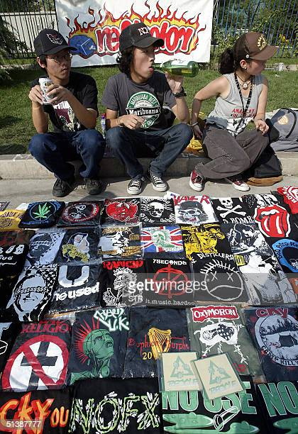 Young Chinese rock and roll fans sell various t'shirts featuring the western rock culture at a park in Beijing 03 October 2004 during a rock concert...