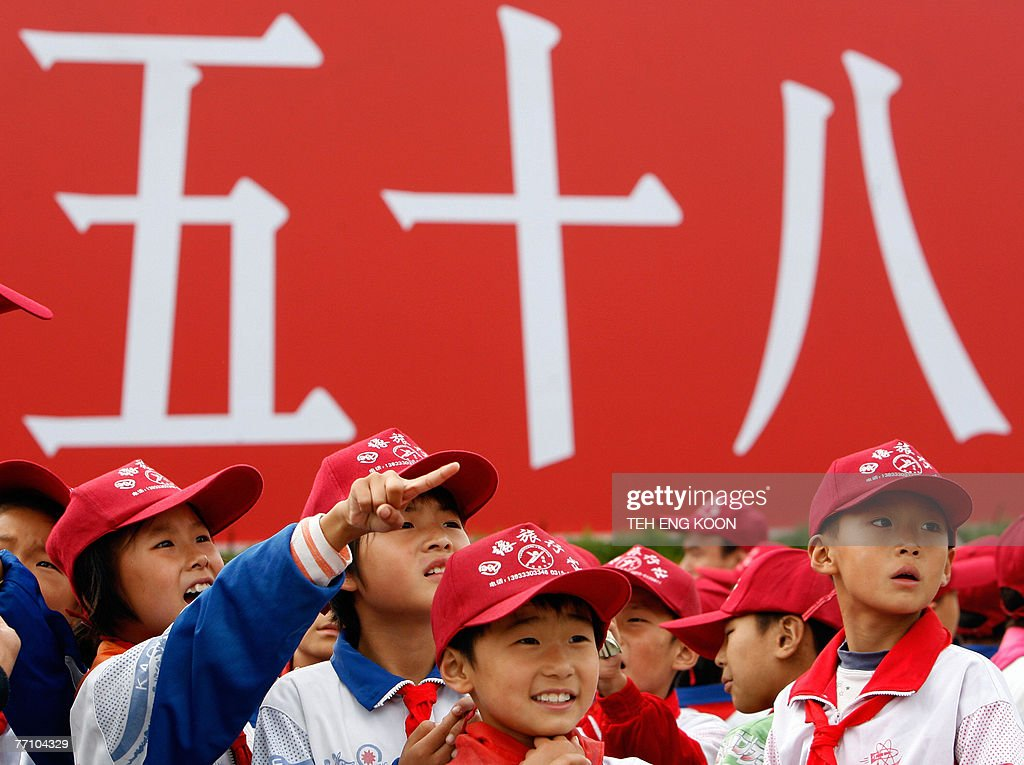 Young Chinese school children stand in front of a billboard of China 58th National Day celebration displayed at the Tiananmen Square in Beijing, 29 September 2007. The Chinese capital is gearing up for its 58th National Day celebration 01 October and the 17th Communist Party Congress in mid-October, which could lead to personnel changes in the top echelons of power and will set China's political and economic course for the next five years. AFP PHOTO/TEH ENG KOON