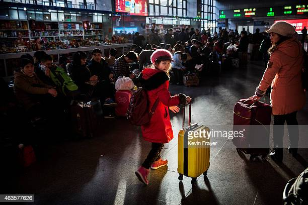 A young Chinese traveler wheels her bag as others wait in the departure area for a train at a local railway station on February 16 2015 in Beijing...