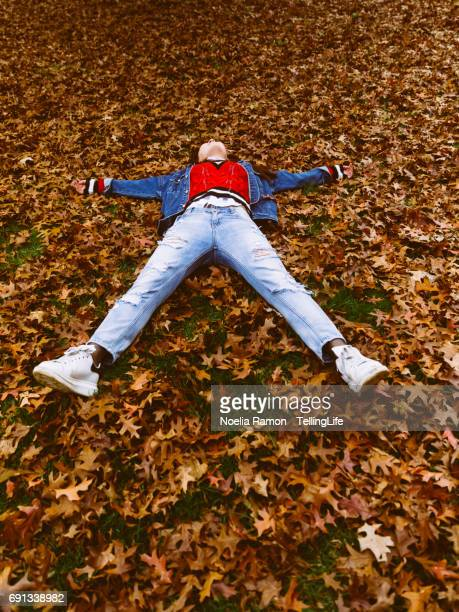 A young Chinese woman laying down and playing with autumn leaves