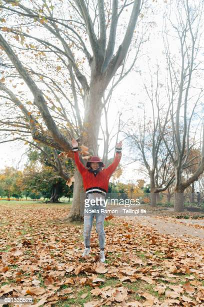 A young Chinese woman playing with autumn leaves