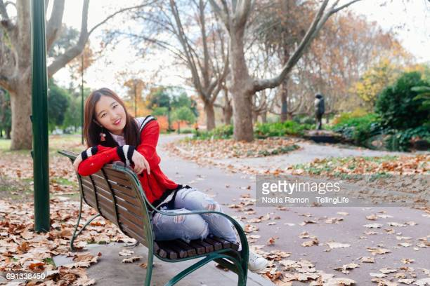 A young Chinese woman seating in a bench in autumn