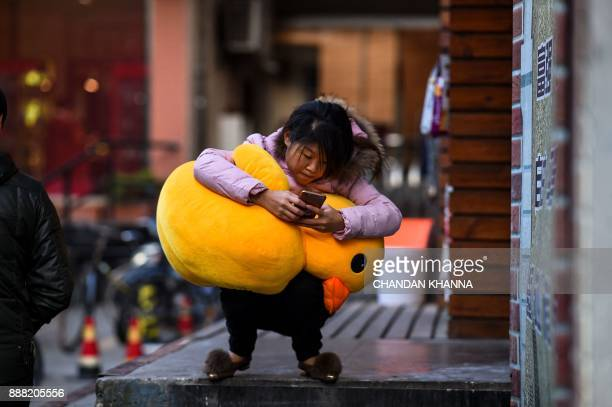 A young Chinese woman squats with a stuffed toy on her lap while using her mobile phone in Shanghai on December 8 2017 / AFP PHOTO / CHANDAN KHANNA