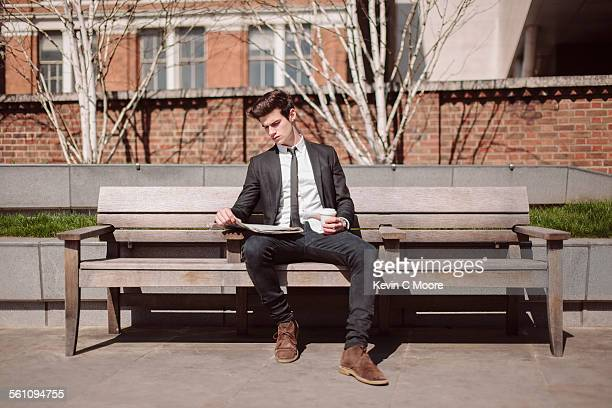 Young city businessman reading newspaper on bench