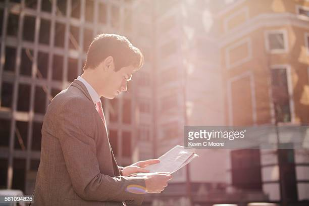 Young city businessman reading newspaper whilst walking
