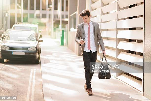 Young city businessman reading smartphone texts whilst walking outside office