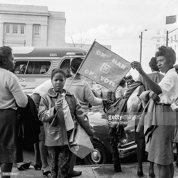 A young Civil Rights activist holds a flag on the steps of the Dexter Avenue Baptist Church on the day before the Selma to Montogmery March arrived...