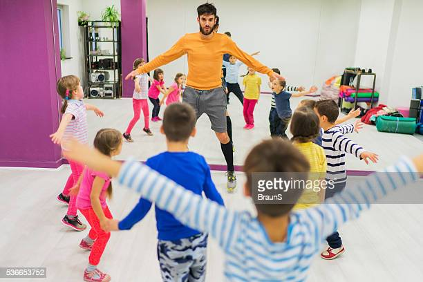Young coach exercising with group of small kids.