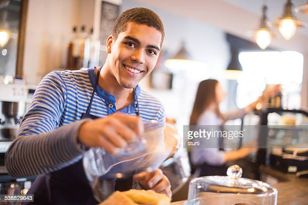 young coffee shop waiter shows off his flapjacks