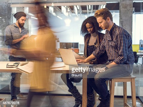 Young colleagues using laptop in the office among blurred people.