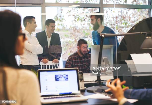 Jungen Kollegen mit laptop im Büro zu verschwommene Personen.