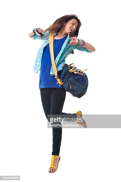 Young college girl dancing while listening music over white background