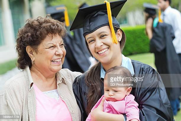Junge college-Absolventen mit Mama und baby Tochter am Abschlussfeier