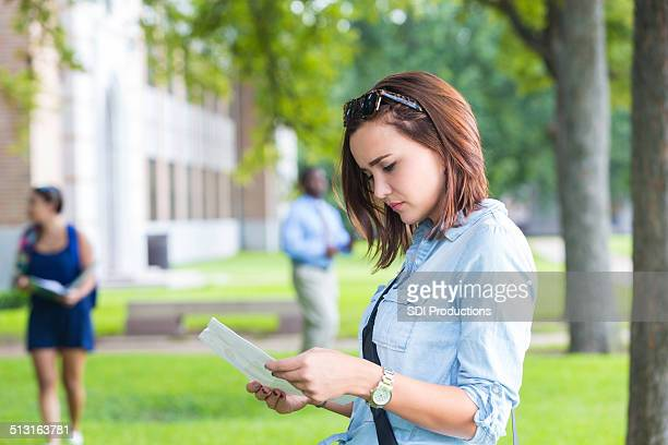 Young college student studying class schedule or campus map