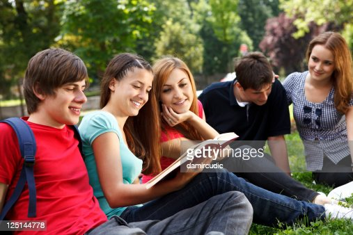 Young college students relaxing outdoors : Stock Photo