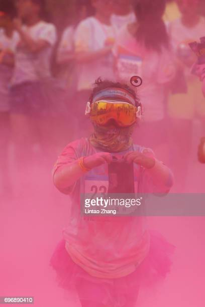 A young competitors run through the pink colour station during the Colour Run at the Beijing International Garden Expo park on June 17 2017 in...