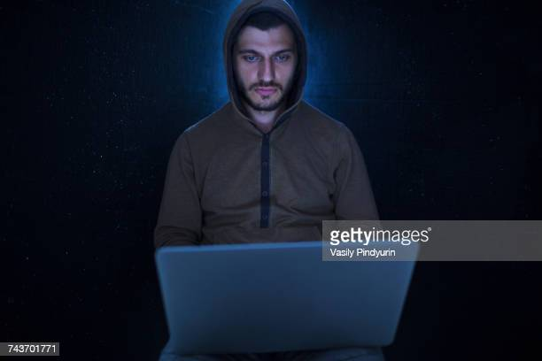 Young computer hacker wearing hooded shirt using laptop against black background
