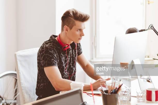 Junge Programmierer arbeiten an seinem Schreibtisch