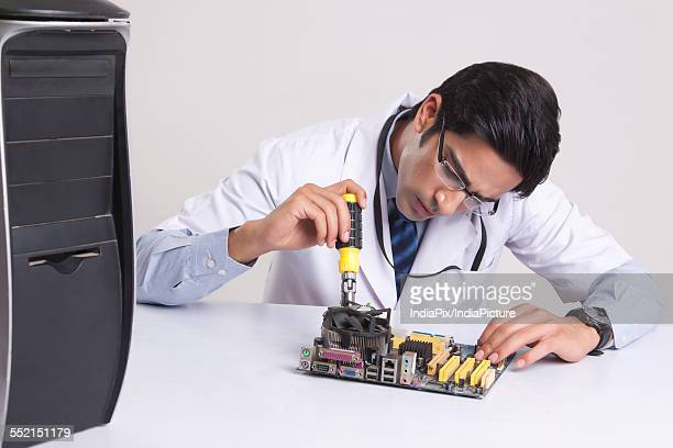 Young computer technician working on mother board against gray background