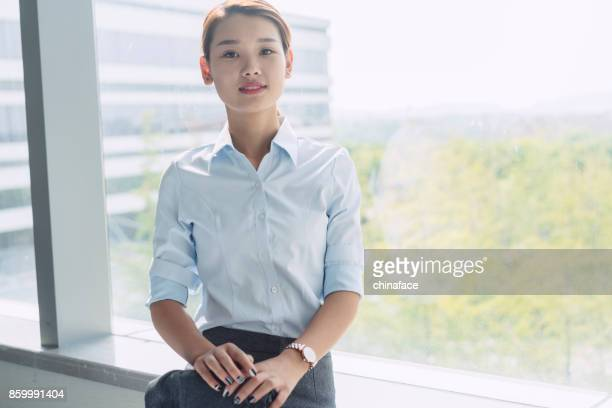 young confident business woman leaning on window sill