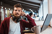 Young handsome confident guy in brown hoodie working in office using headset and laptop