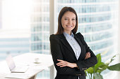 Portrait of young smiling businesswoman standing in modern office interior with arms crossed, looking at camera. Great career achievements, confident self-made woman and motivated professional