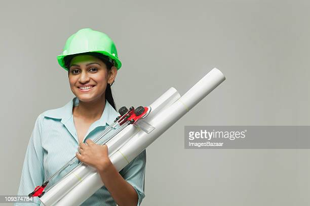Young construction engineer holding plans and looking at camera, studio shot