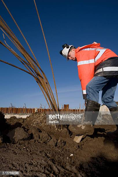 Jeune Travailleur de la construction sur un bâtiment brasier, creuser avec Pelle