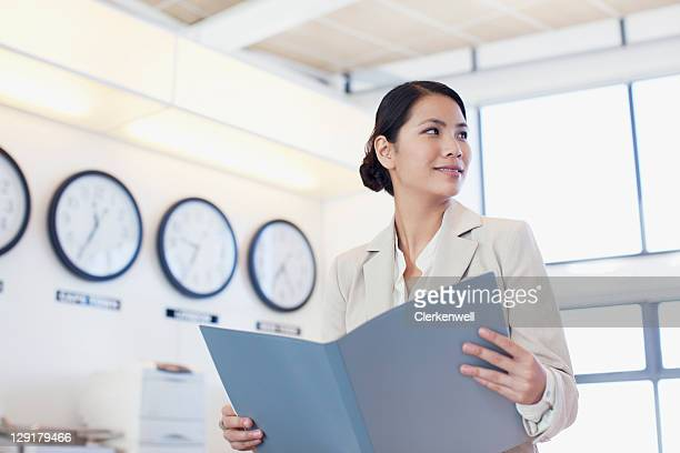 Young contemplative businesswoman sitting on office desk