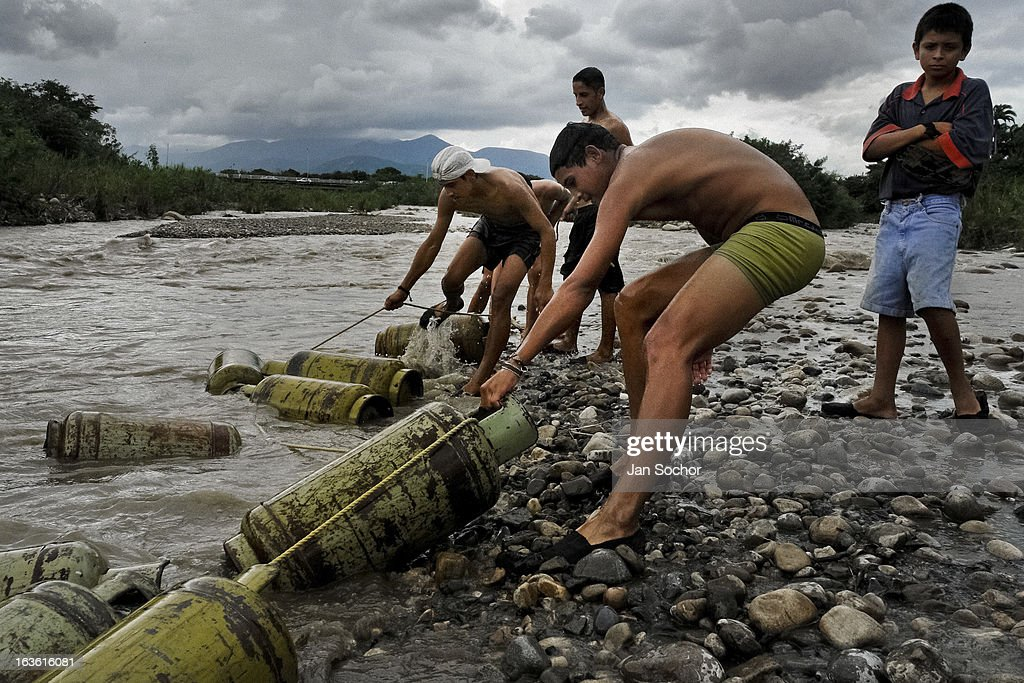 Young contraband smugglers pull gas cylinders out of the river Tachira on the Colombia-Venezuela border, on 3 May 2006 in La Parada, Colombia. Venezuelan gasoline, being 20 times cheaper than in Colombia, is the most wanted smuggling item, followed by food and car parts, while reputable Colombian clothing flow to Venezuela. There are about 25,000 barrels of gasoline crossing illegally the Venezuelan border every day. The risky contraband smuggling, especially during the rainy season when the river rises, makes a living to hundreds of poor families in communities on both sides of the frontier.