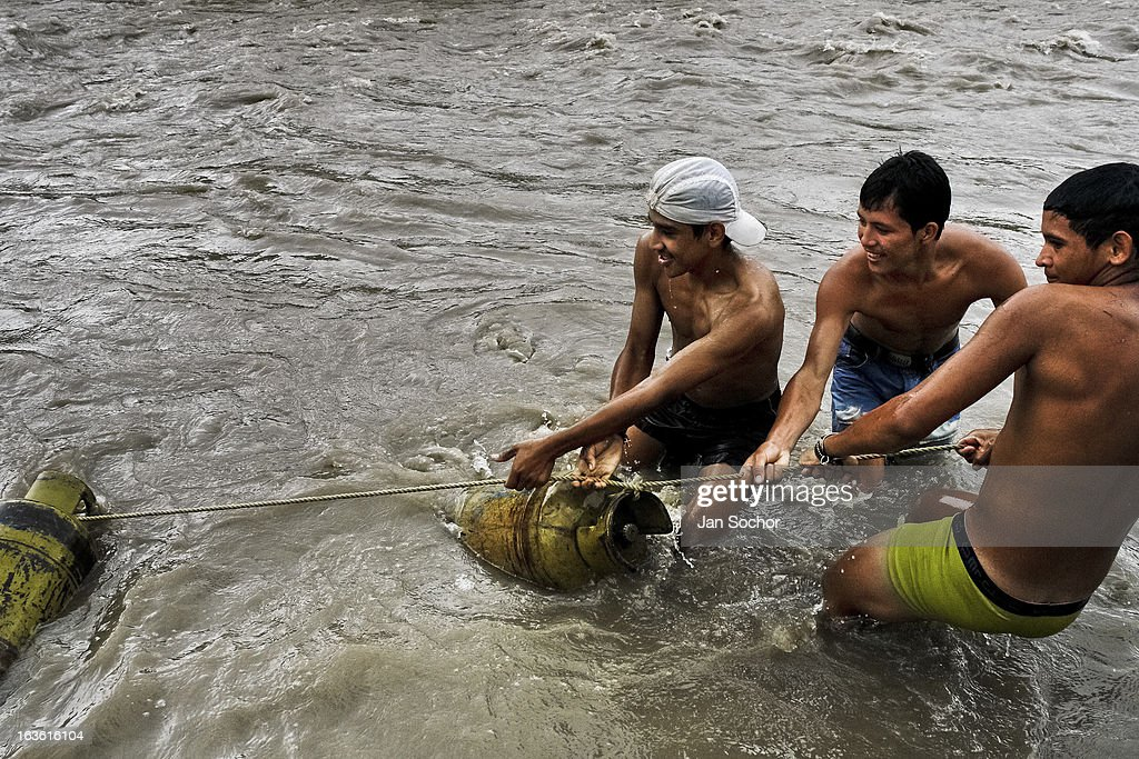 Young contraband smugglers pull gas cylinders out of the river Tachira on the Colombia-Venezuela border, on 3 May 2006 in La Parada, Colombia. Venezuelan gasoline, being 20 times cheaper than in Colombia, is the most wanted smuggling item, followed by food and car parts, while reputable Colombian clothing flow to Venezuela. There are about 25,000 barrels of gasoline crossing illegally the Venezuelan border every day. The risky contraband smuggling, especially during the rainy season when the river rises, makes a living to hundreds of poor families in communities on both sides of the frontier. (Photo by Jan Sochor/Latincontent/Getty Images))