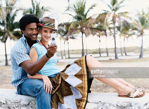 Young Cool Couple  Sitting on a Wall Taking a Picture of Themselves with a Mobile Phone