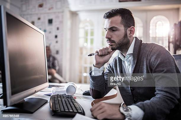 Young corporate businessman thinking of new ideas at office.