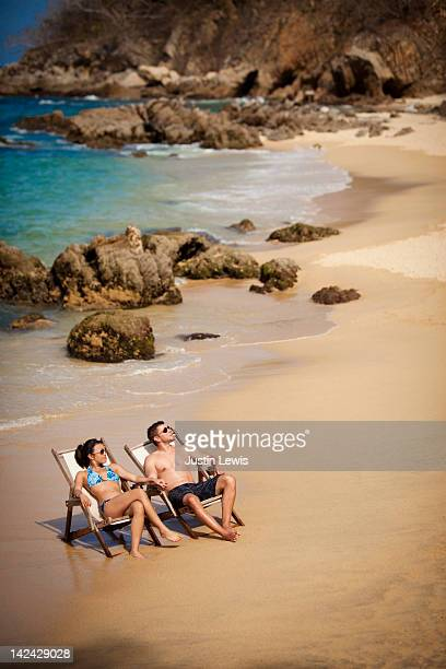 Young coupld relaxing in charis on rocky beach