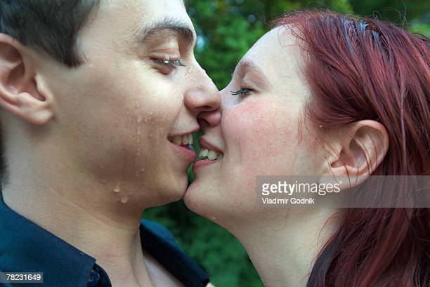 young couple about to kiss in the rain