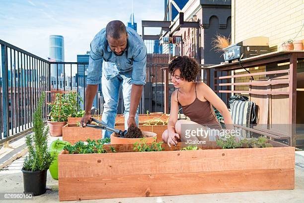 Young couple addding soil to a planter box