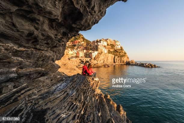 A young couple admiring the sunset from the rocks in Manarola. Manarola, Cinque terre, La Spezia, Liguria.